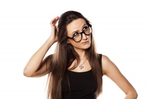 unsure young woman scratching her head